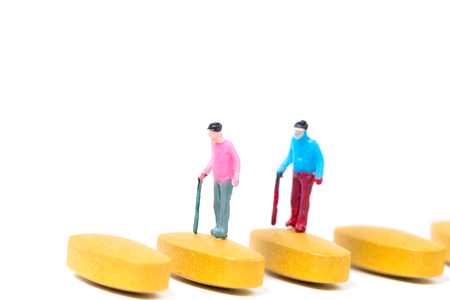 Miniature people, small figure old man or patient holding walking stick with vitamin C pill or tablets on white background, health care and healthy concept.