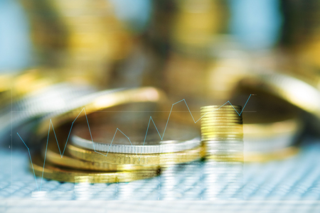 Double exposure of coin stacks with financial graph and copy space for business and financial concept idea. shallow focus. Stock Photo