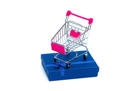 Blue gift box with ribbon bow and shopping cart or supermarket trolley isolated on whtie background with copy space for season or greeting and merry concept, present on holiday.