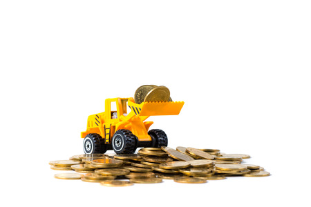 Mini bulldozer truck loading stack coin with pile of gold coin, isolated on white background with copy space, business finance and banking industrial concept idea. Reklamní fotografie