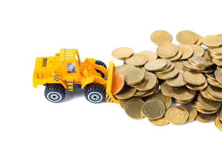 Mini bulldozer truck loading stack coin with pile of gold coin, isolated on white background with copy space, business finance and banking industrial concept idea. Archivio Fotografico
