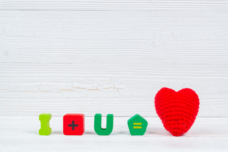 Valentine card with Love text and red knitting heart on white wooden background and copy space for add text and picture, love and valentine day concept idea.