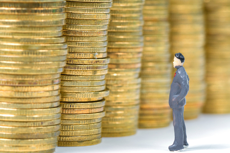 Figure miniature businessman or small people standing with stack of coin on white background for money and financial business success concept.