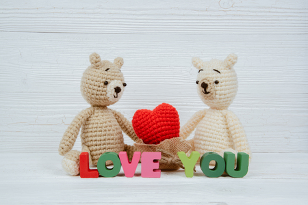 Sweet couple teddy bear doll in love with Love text and red knitting heart on white wooden background and copy space for add text and picture, love and valentine day concept idea.