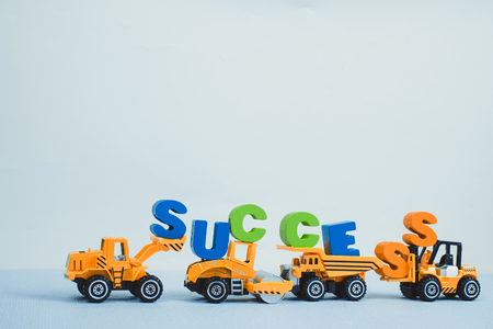 Mini forklift bulldozer truck and road roller machine with text SUCCESS, motivational business and financial concept idea.
