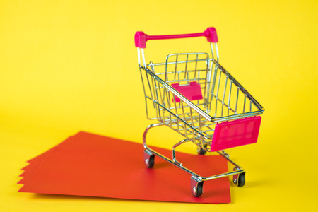 Shopping cart or supermarket trolley and blank red envelop on yellow background with space for add text, Chinese new year and shopping concept idea. Archivio Fotografico