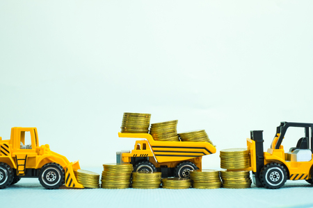 forklift bulldozer truck and road roller machine with pile of gold coin, with copy space, business finance and banking industrial concept idea.