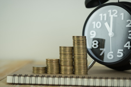 Steps of coins stack with vintage alarm clock and pen, notebook paper on wooden working table with copy space for text, financial and business planning concept idea. Stock Photo