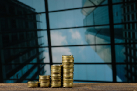 Step of coin stack on top wooden working table with city and office building background, business and financial concept idea.