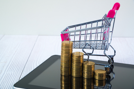 Step of coin stack and shopping cart or supermarket trolley on tablet computer screen on white working table, business and finance concept idea. Stock Photo