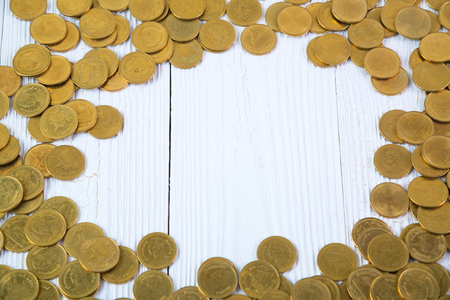 Piles of coins on white wood working table, business and financial concept idea.