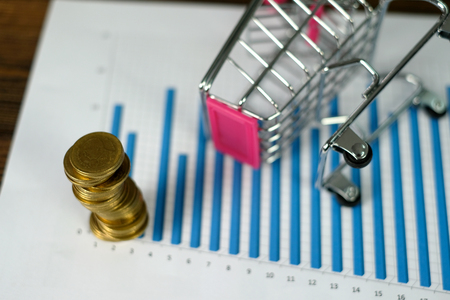 Step of coins stacks with trolley and notebook laptop computer and financial graph on paper on working table, business planning vision and finance analysis concept idea. and copy space for add text.