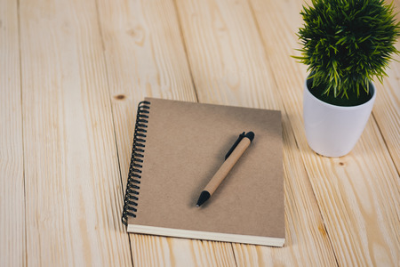 Little decorative tree in white vase and notebook with pen on wooden table with copy space. background.