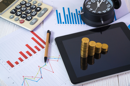 Step of coins stacks and alarm clock with tablet computer and financial graph, business planning vision and finance analysis concept idea.