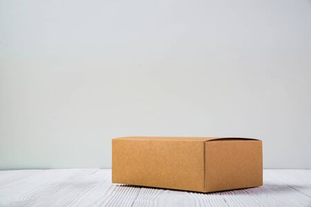 Empty Package brown cardboard box or tray on bright white wooden table with copy space.