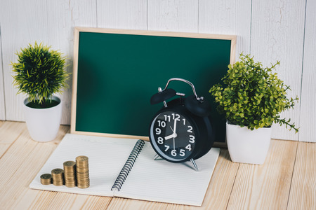 Step of coins stacks and alarm clock with green chalkboard, notebook and financial graph, business planning vision and finance analysis concept idea. Stock Photo