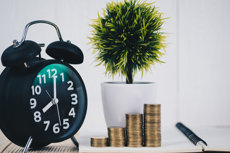 Step of coins stacks and alarm clock, notebook and financial graph, business planning vision and finance analysis concept idea.