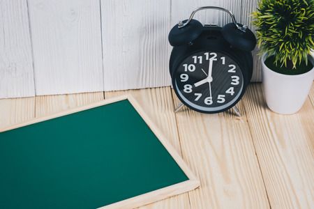 Blank green chalkborad with wood frame and little decorative tree in white vase and vintage alarm clock on wooden table with copy space for add text.