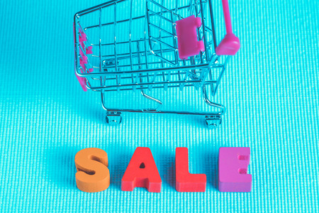 Sale colorful wooden text and shopping cart or supermarket trolley on blue background with copy space, shopping discount and merketing concept idea. template for add text or photo.