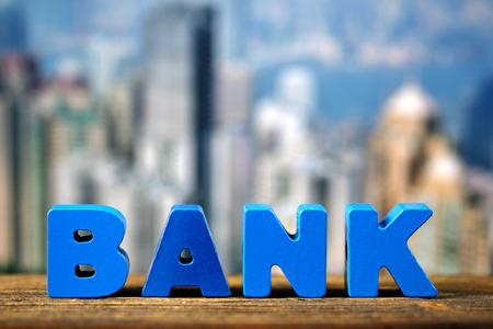 BANK text on top wooden working table with city and office building background, business and financial concept idea. Stock Photo