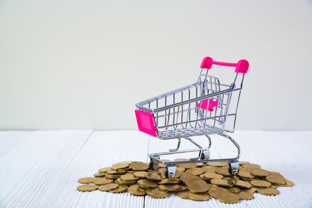 Piles of coins and shopping cart or supermarket trolley on white wood working table, business and financial concept idea.
