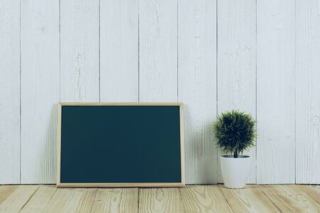 Blank green chalkborad with wood frame and little decorative tree in white vase on wooden table with copy space for add text. Stock Photo