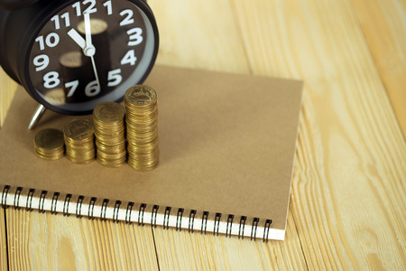 Steps of coins stack with vintage alarm clock and pen, notebook paper on wooden working table with copy space for text, financial and business planning concept idea. vintage tone.