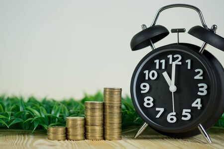 Steps of coins stack with vintage alarm clock on wooden working table with copy space for text, financial and business planning concept idea.