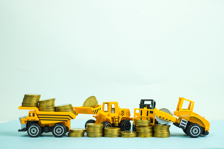 Mini forklift bulldozer truck and road roller machine with pile of gold coin, with copy space, business finance and banking industrial concept idea. Stock Photo