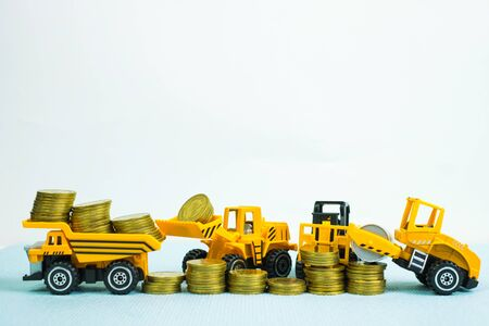 Mini forklift bulldozer truck and road roller machine with pile of gold coin, with copy space, business finance and banking industrial concept idea. Reklamní fotografie