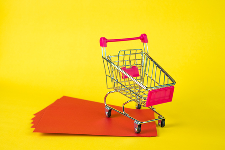 Shopping cart or supermarket trolley and blank red envelop on yellow background with space for add text, Chinese new year and shopping concept idea. Stock Photo