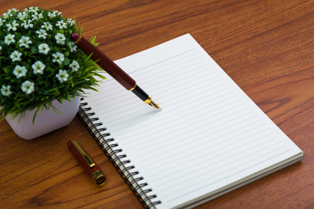 Fountain pen or ink pen with notebook paper and little decoration tree in white vase on wooden working table with copy space, office desk concept idea.