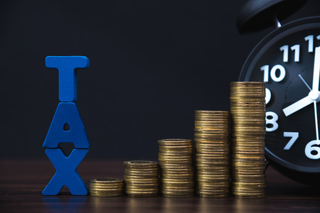 Time to pay TAX concept. TAX alphabet with stack of coin and vintage alarm clock in dark background, business and financial concept idea.