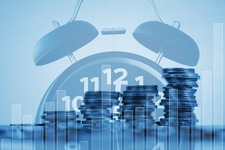 Double exposure of coin stack and alarm clock with city background and financial graph, business finance concept idea.