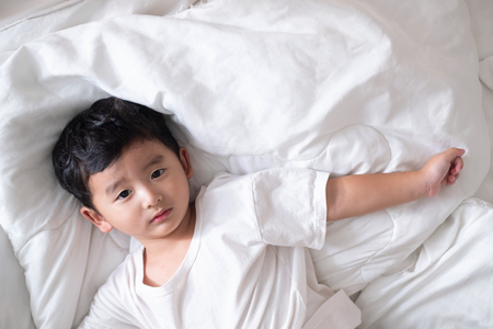 3 years old little sick or illness Asian boy at home on the bed, sad kid laying resting on white bed with pillow and blanket, top view with copy space for add text.