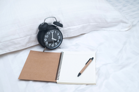 Diary or notebook and vintage alarm clock on bed in bedroom at home or hotel, working or note something before sleep.