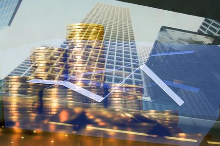 Pila di doppia esposizione di moneta con il grafico finanziario sopra l'idea di concetto finanziario e del fondo dell'edificio per uffici e della città.