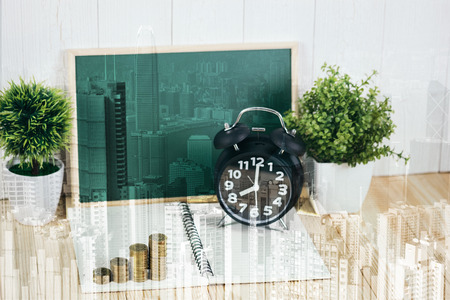 Double exposure coins stacks and alarm clock with green chalkboard, notebook and financial graph on city background, business planning vision and finance analysis concept idea. Stock Photo