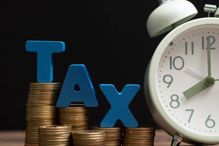 Time to pay TAX concept. TAX alphabet with stack of coin and vintage alarm clock on wooden working table in dark background, business and financial concept idea. Stock Photo