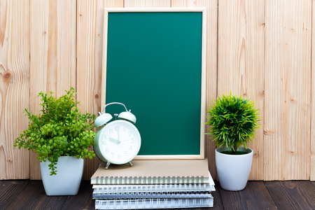 Blank green chalkborad and little tree with vintage alarm clock and notebook paper pen on wooden table with copy space for add text.