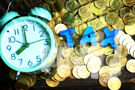 Double exposure of TAX alphabet with stack of coin and vintage alarm clock on city background, business and financial idea. Time to pay TAX concept.