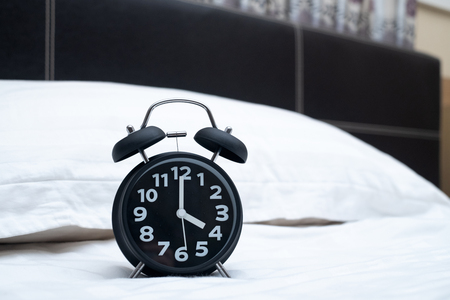 Vintage alarm clock on the bed in bedroom at home, wake up or bed time concept idea. Stock Photo