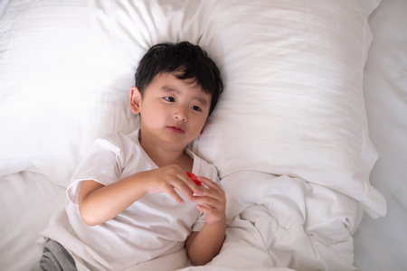 3 years old little cute Asian boy in white shirt at home on the bed, kid lying playing and smiling on white bed with pillow and blanket, top view with copy space for add text.