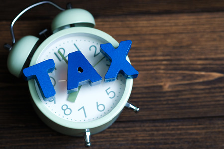 Time to pay TAX concept. TAX alphabet and vintage alarm clock on wooden working table in dark background, business and financial concept idea.