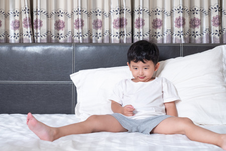 3 years old little cute Asian boy at home on the bed, kid lying playing and smiling on white bed with pillow and blanket, with copy space for add text. Stock Photo