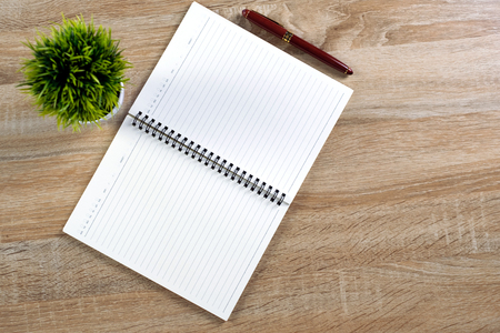 Fountain pen or ink pen with notebook paper and little decoration tree in white vase on wooden working table with copy space, office desk concept idea. top view.