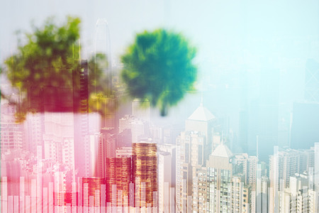 Double exposure of coin stack and little tree on city background with financial graph chart, business planning vision and finance analysis concept idea.