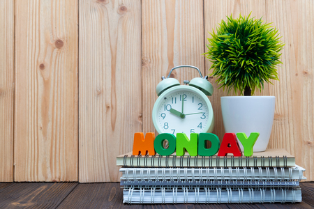MONDAY letters text and notebook paper, alarm clock and little decoration tree in white vase on wooden background, hello Monday concept idea.