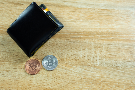 Bitcoin digital currency instead real money, bit-coin with leather wallet or purse on wooden working table, virtual cryptocurrency money business concept idea.