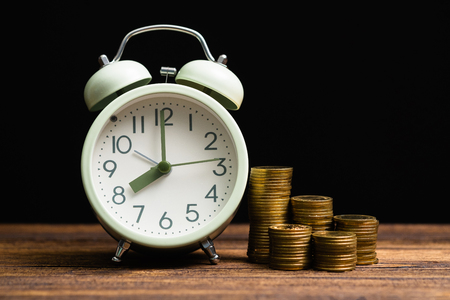 Alarm clock and coins stacks on working table in dark room, time for savings money concept, banking and business concept idea.